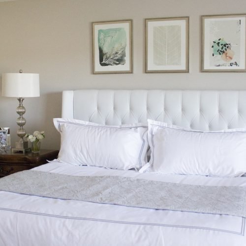 white headboard with art prints above the headboard