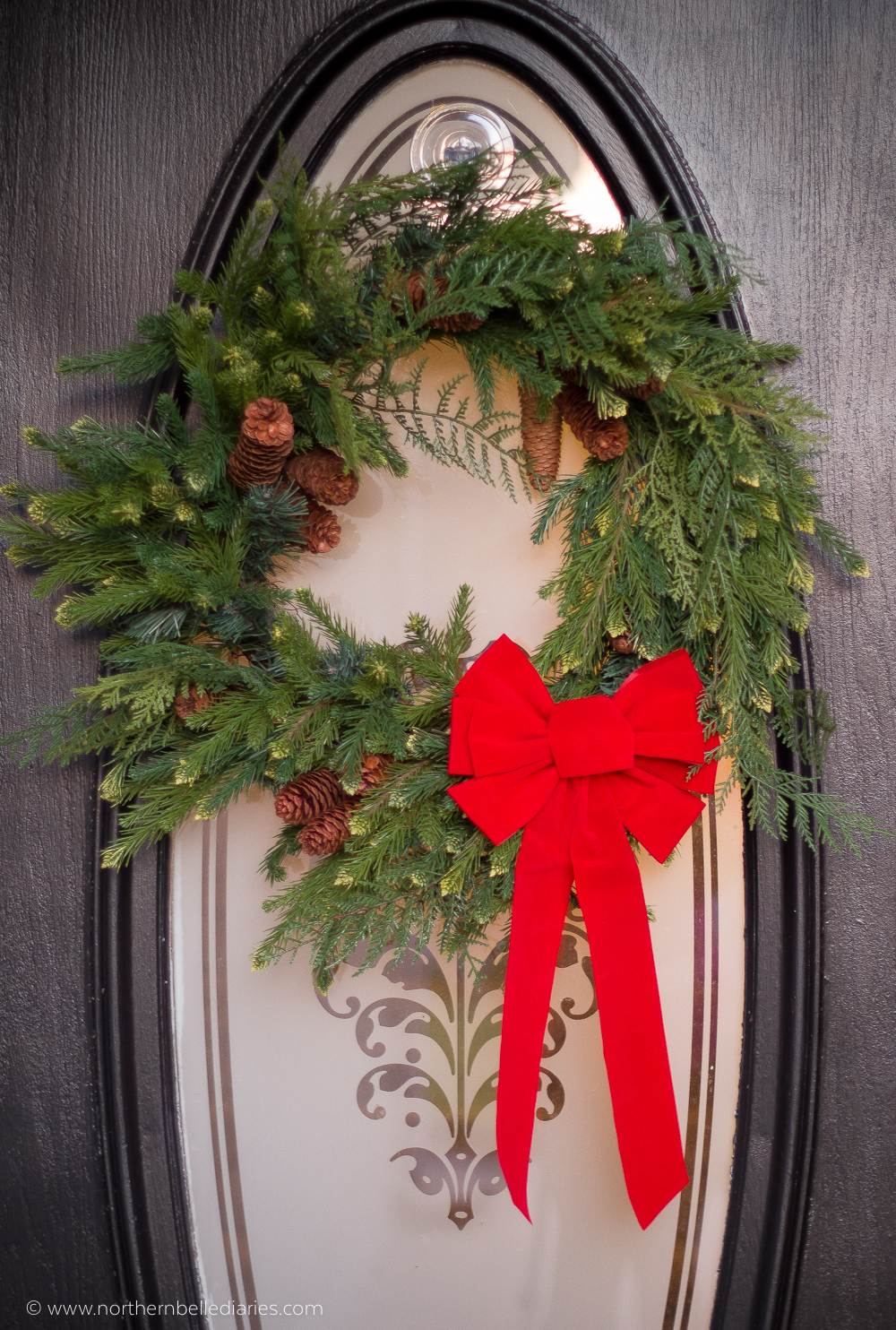 Classic Christmas wreath with red ribbon on black front door #christmas