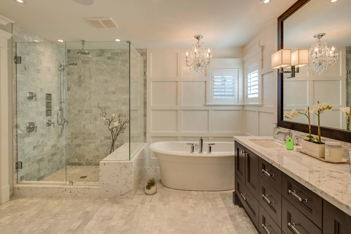 Dreamy bathroom with marble tile, garden tub, dark wood vanity and chandelier and wainscoting