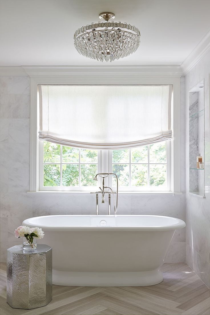 Garden tub with window, marble tile walls, herringbone floor, crystal chandelier