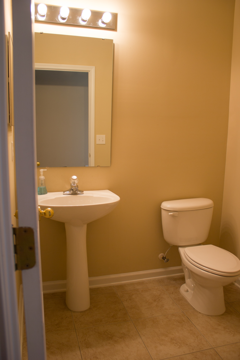 Elegant Half Bath on a Budget using Devine Color Wallpaper | Before: builder grade beige