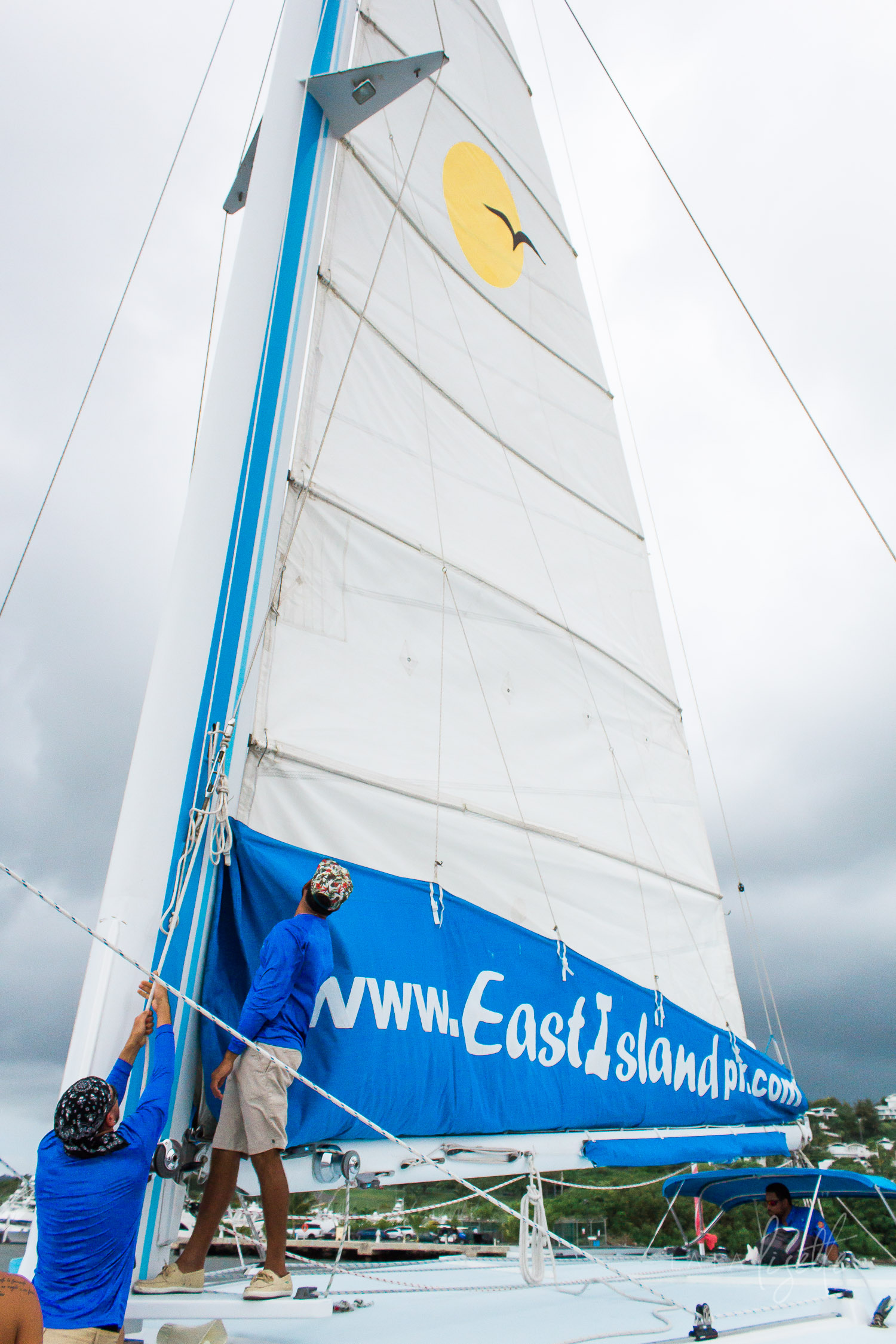 sailors-hoisting-sail-catamaran
