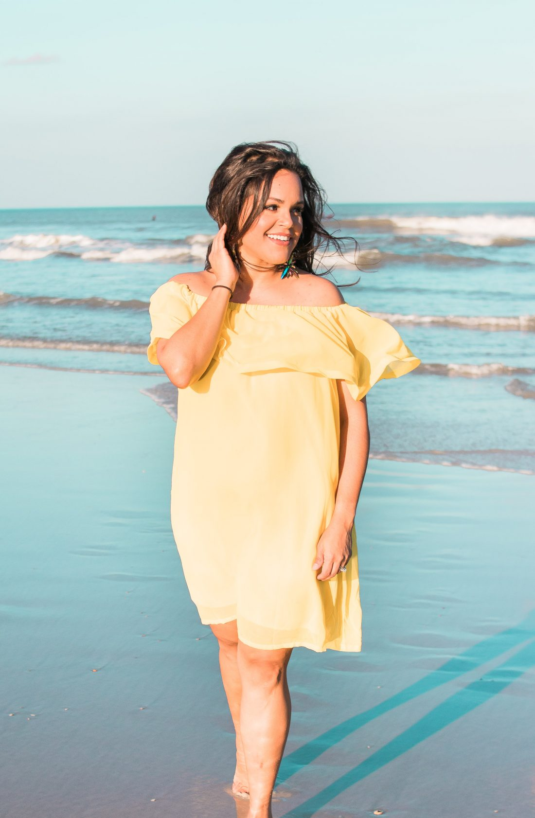 brunette woman standing on beach wearing yellow sundress