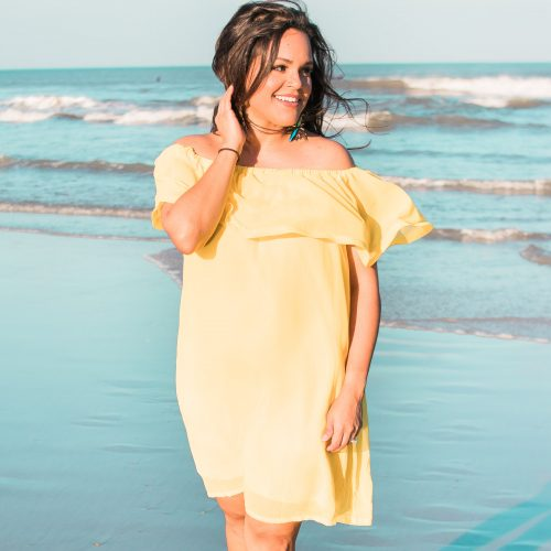 brunette woman standing on beach wearing yellow sundress