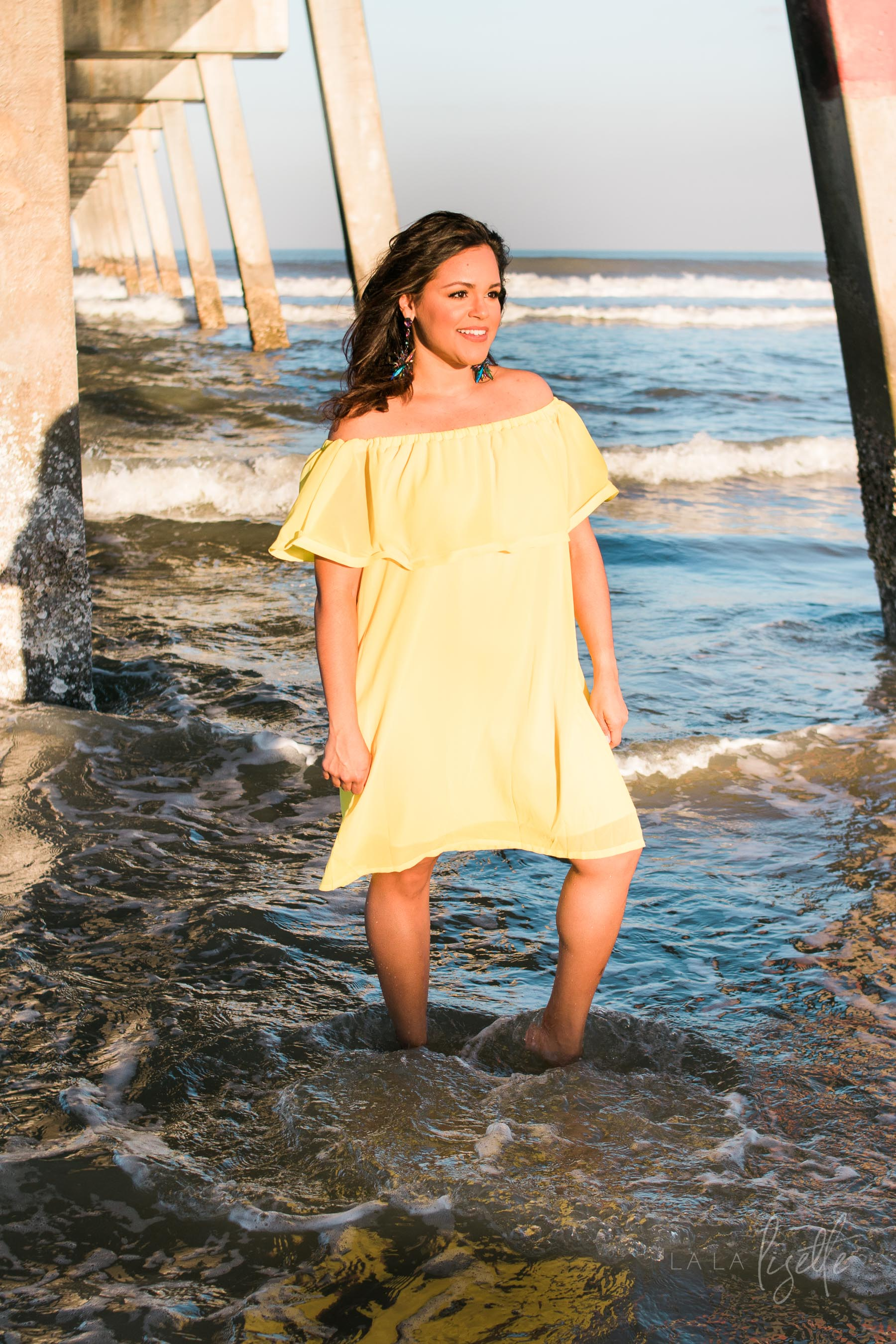 brunette woman standing under pier wearing yellow sundress