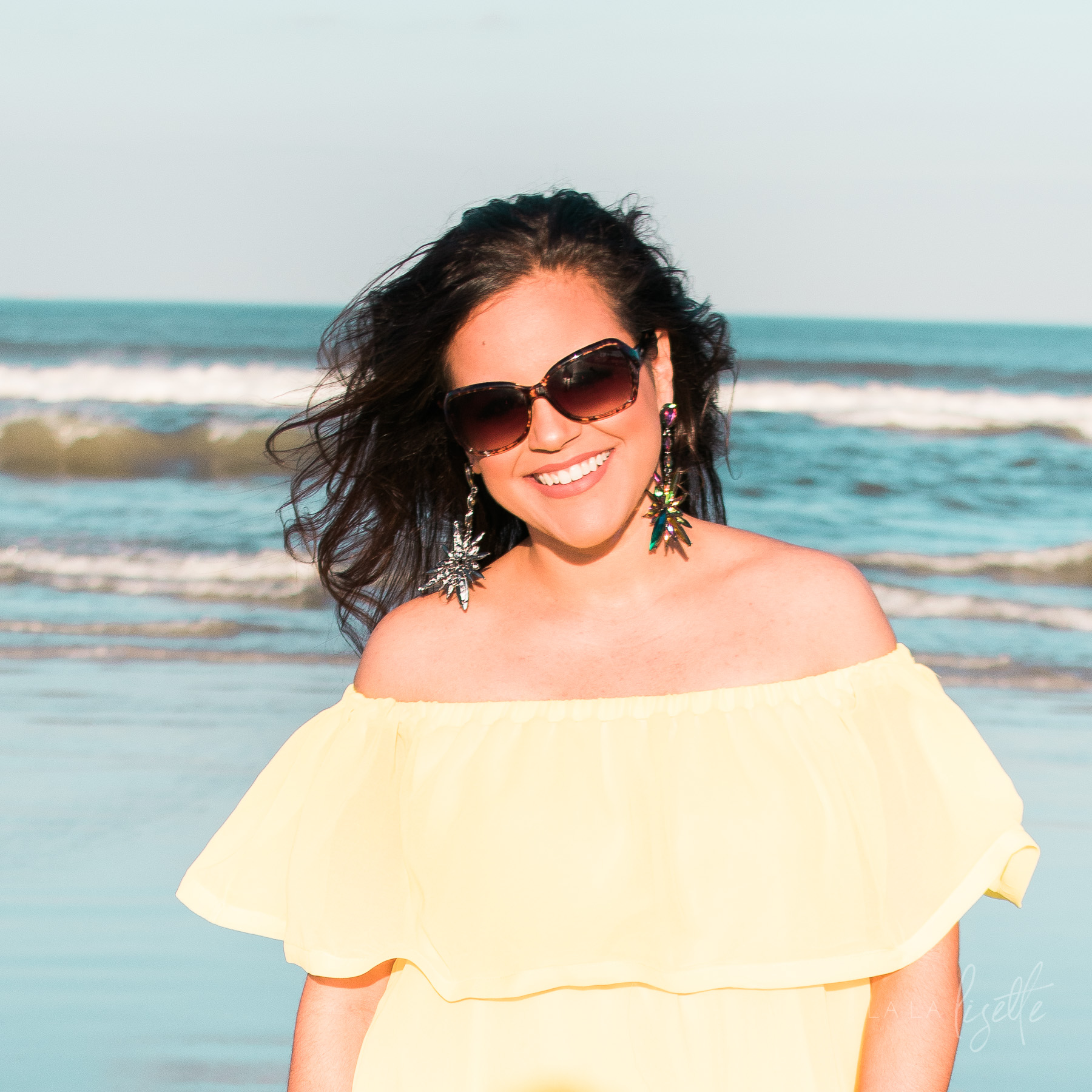 woman standing on beach wearing yellow sundress and sunglasses