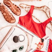 "A flatlay display of festival staple sandals, flat iron, sunglasses, moisturizer, and red retro Jockey underwear with a straw bag that reads ""cabana boy wanted"""
