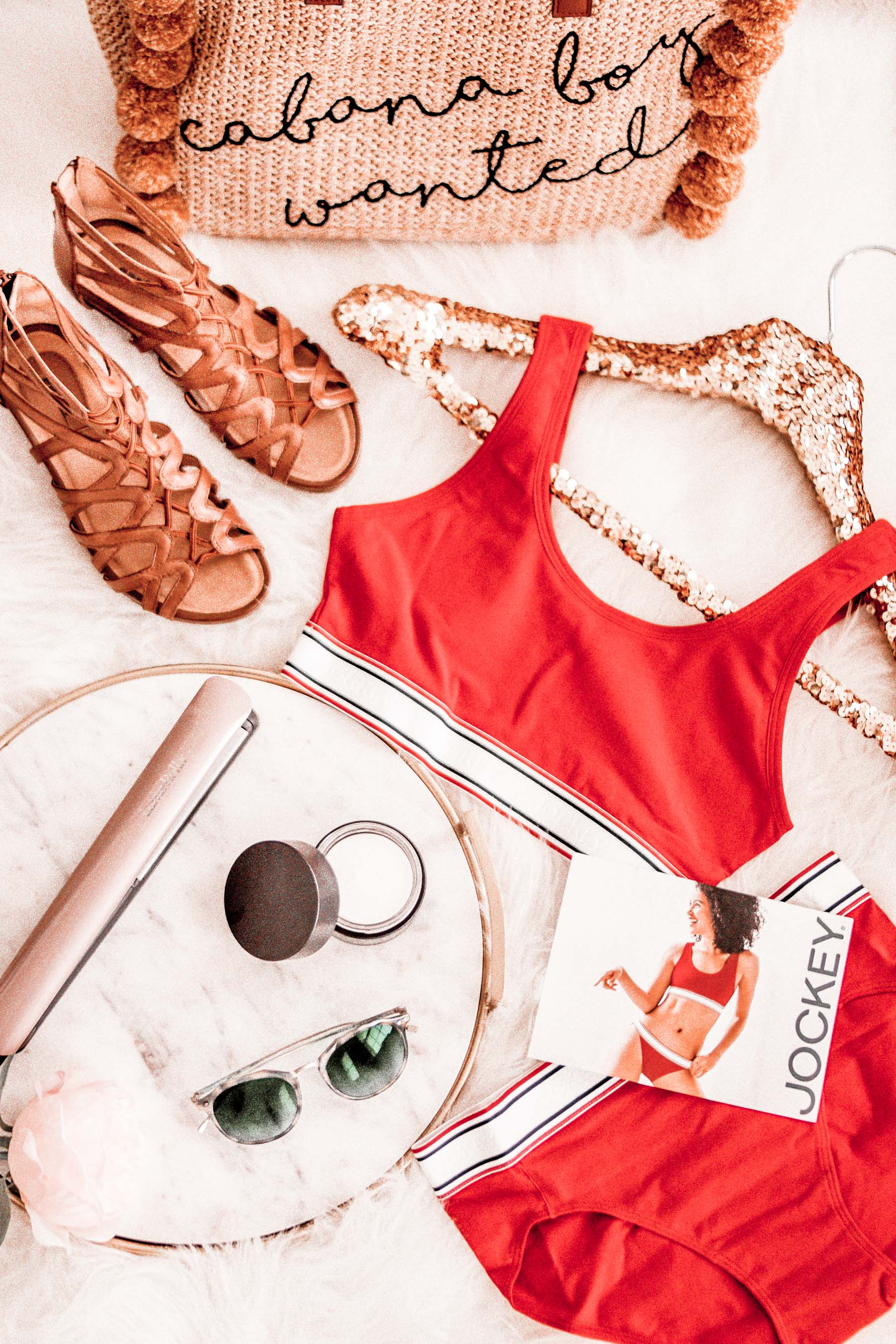 "A flatlay display of festival must haves like staple sandals, flat iron, sunglasses, moisturizer, and red retro Jockey underwear with a straw bag that reads ""cabana boy wanted"""