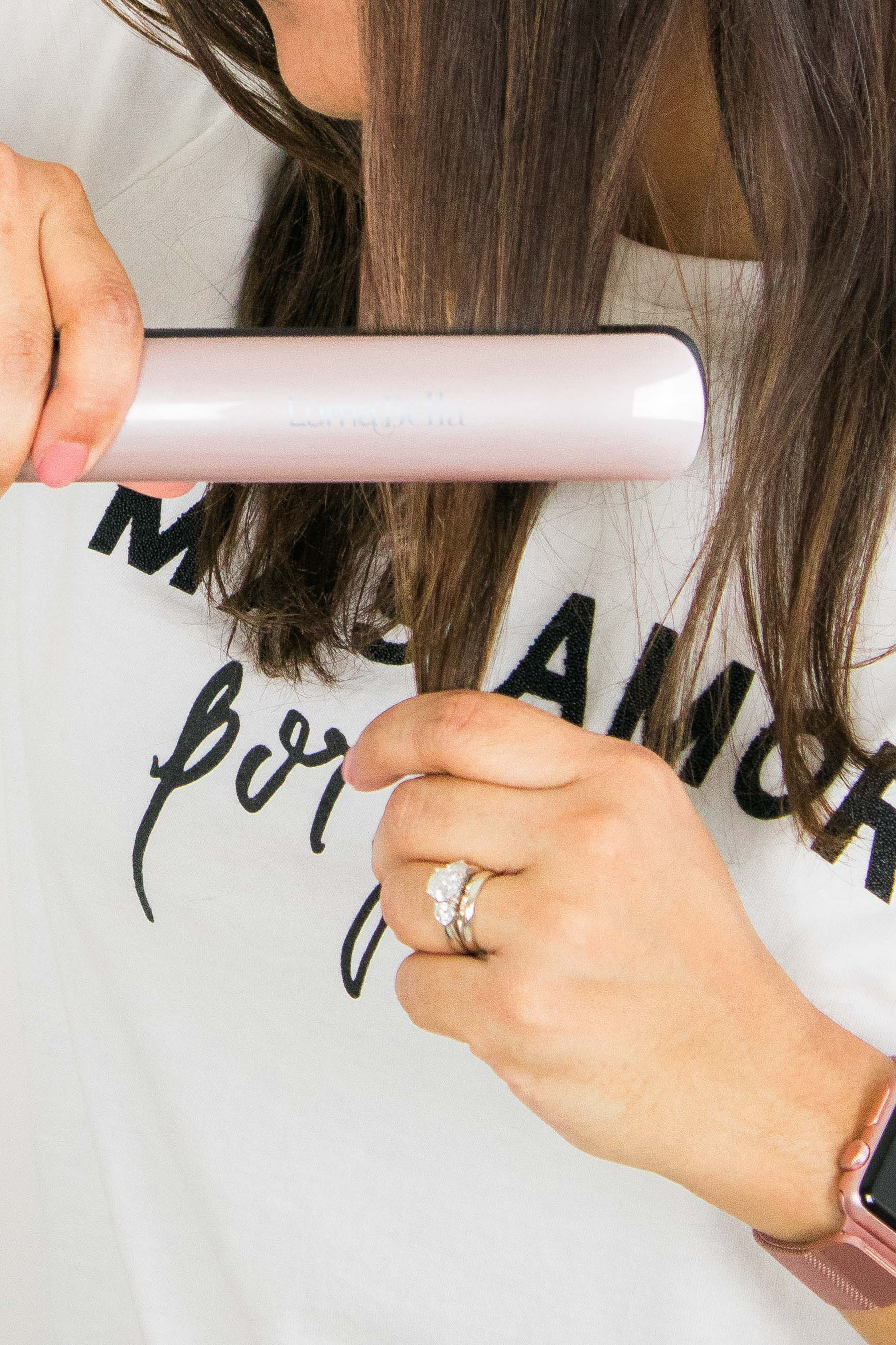 "Woman flat ironing her hair, wearing t-shirt that reads ""Mas Amor por favor"""