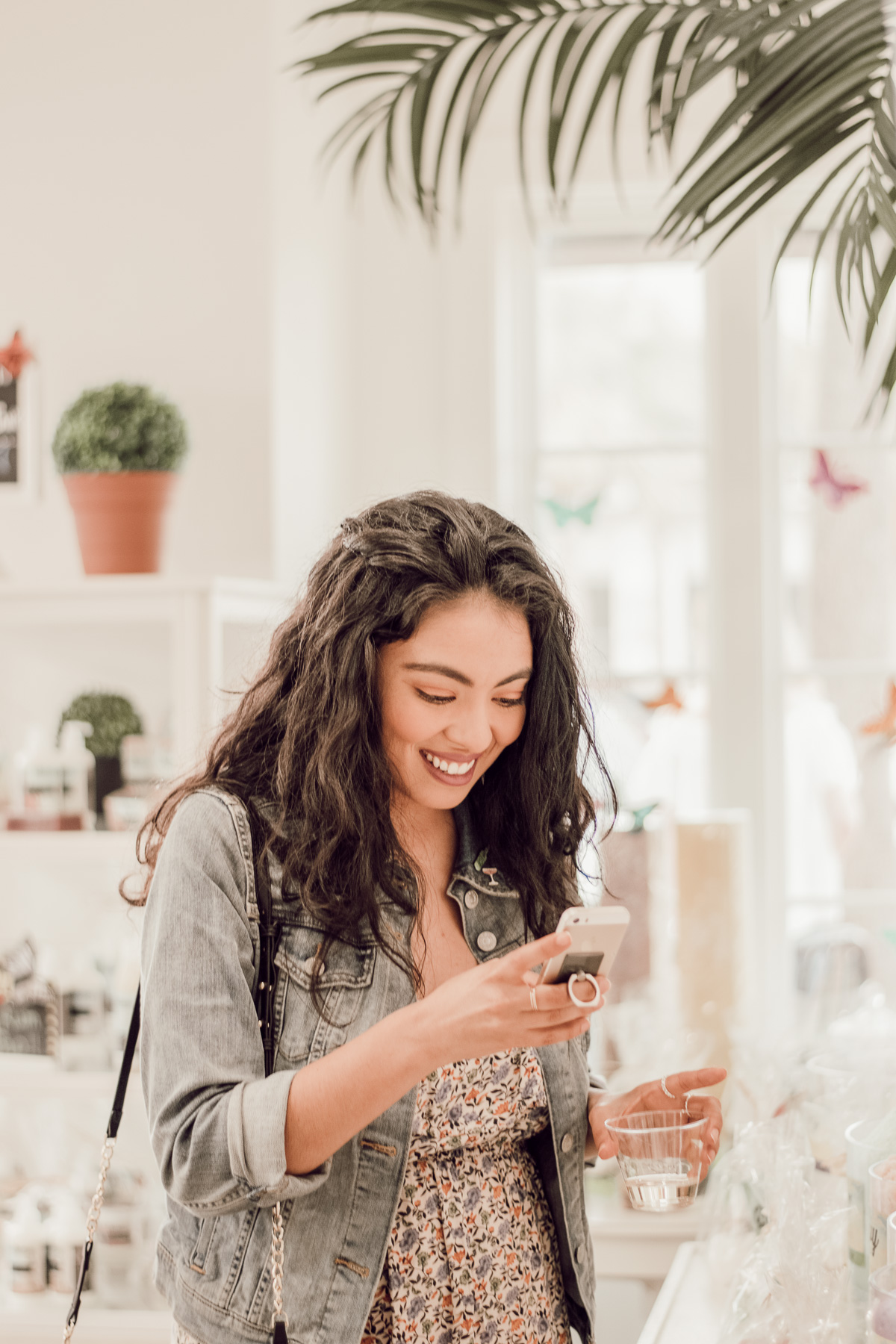 smiling brunette woman looking at iPhone in a shop