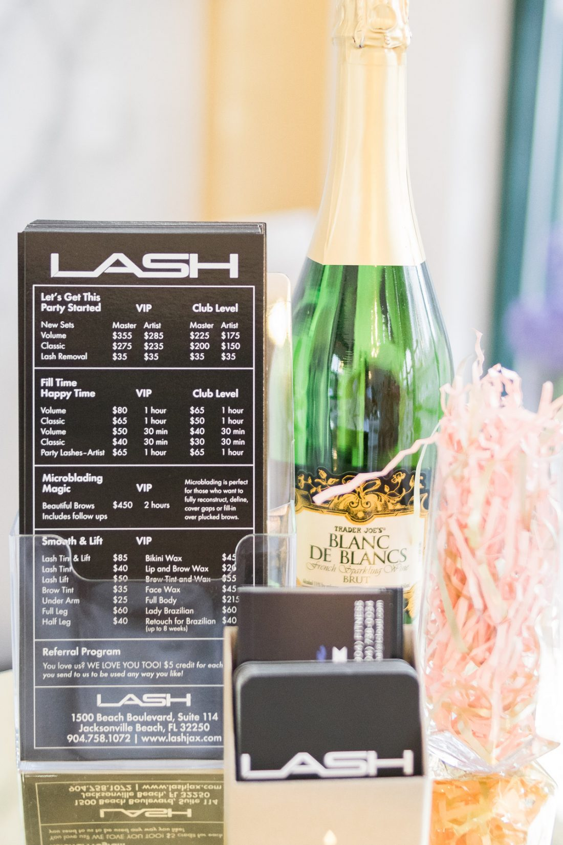 LASH Jax rate sheet next to champagne