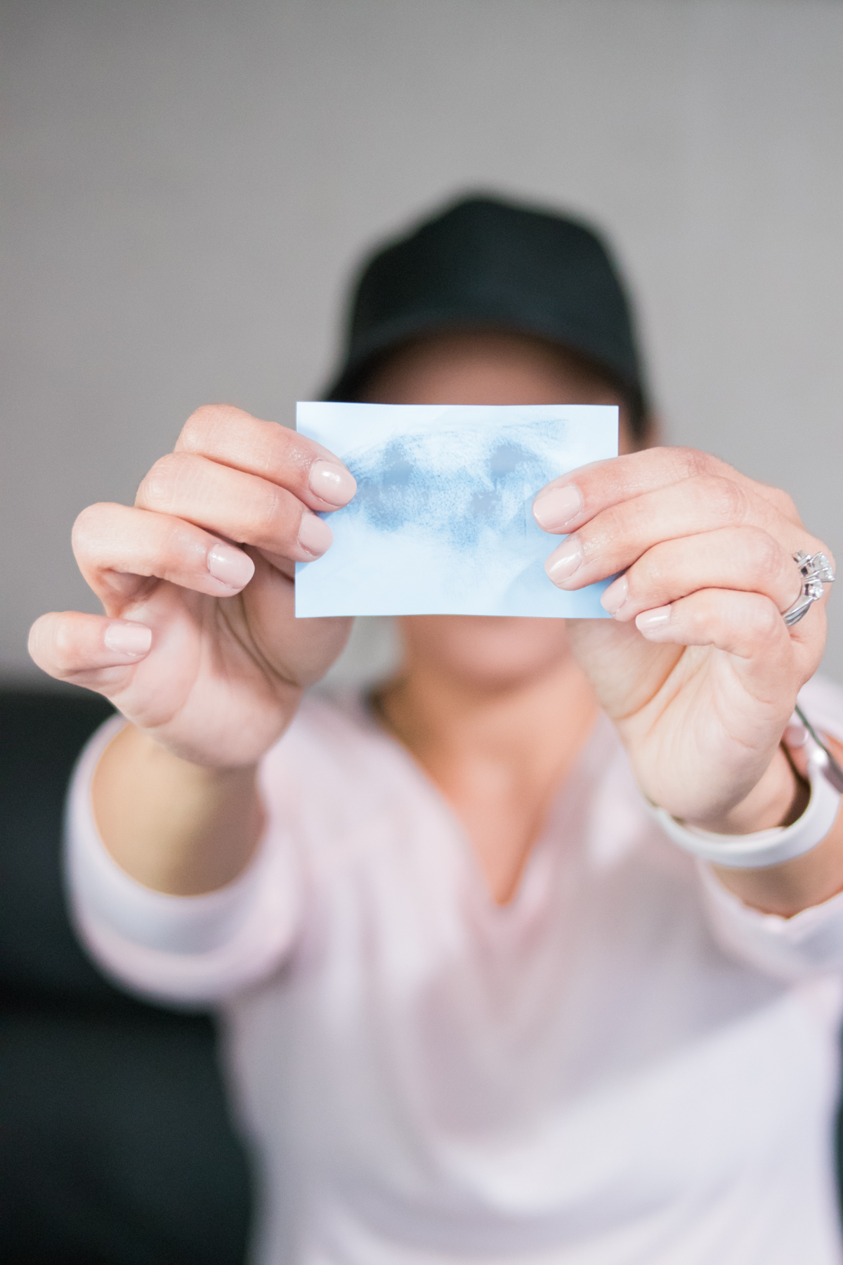 woman holding a used oil blotting sheet excess oil from her face as part of her workout beauty routine