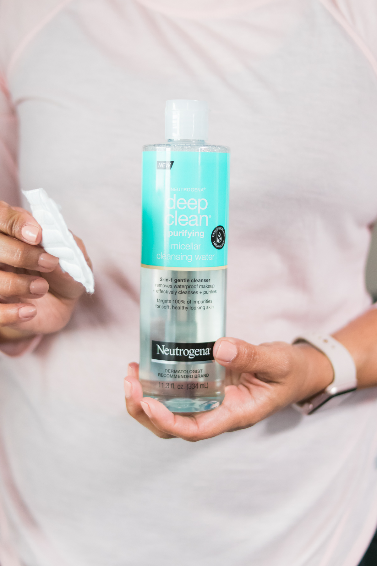 woman holding cotton pad and Neutrogena Deep Clean Purifying micellar cleansing water