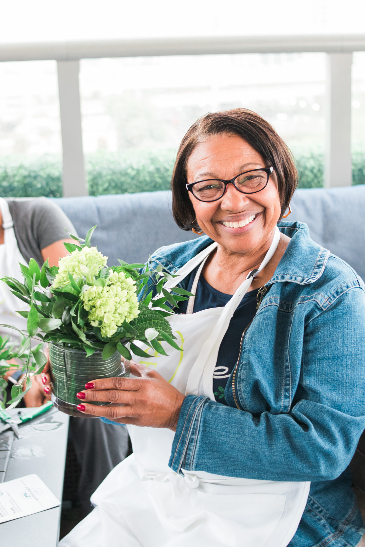 women smiling with her floral arrangement during Alice's Table workshop in Jacksonville, Florida