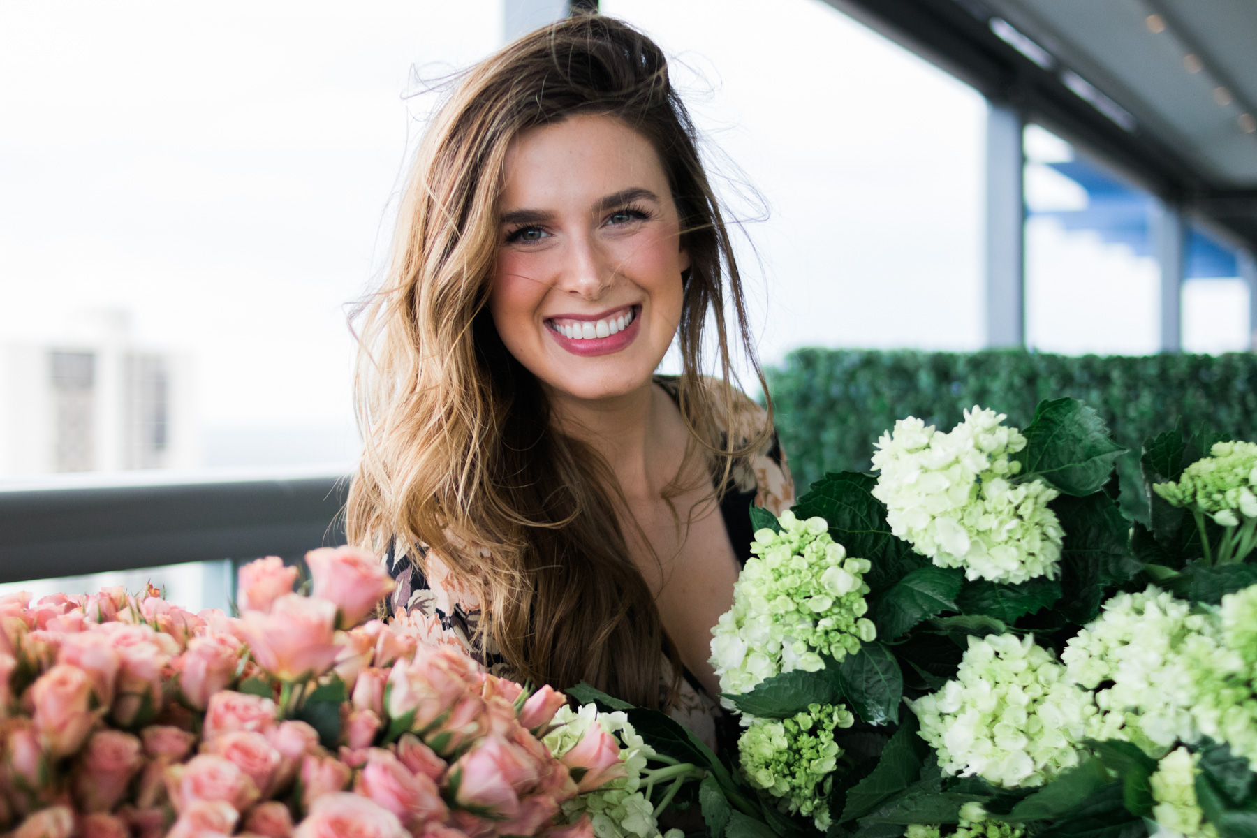 pretty woman smiling with floral display