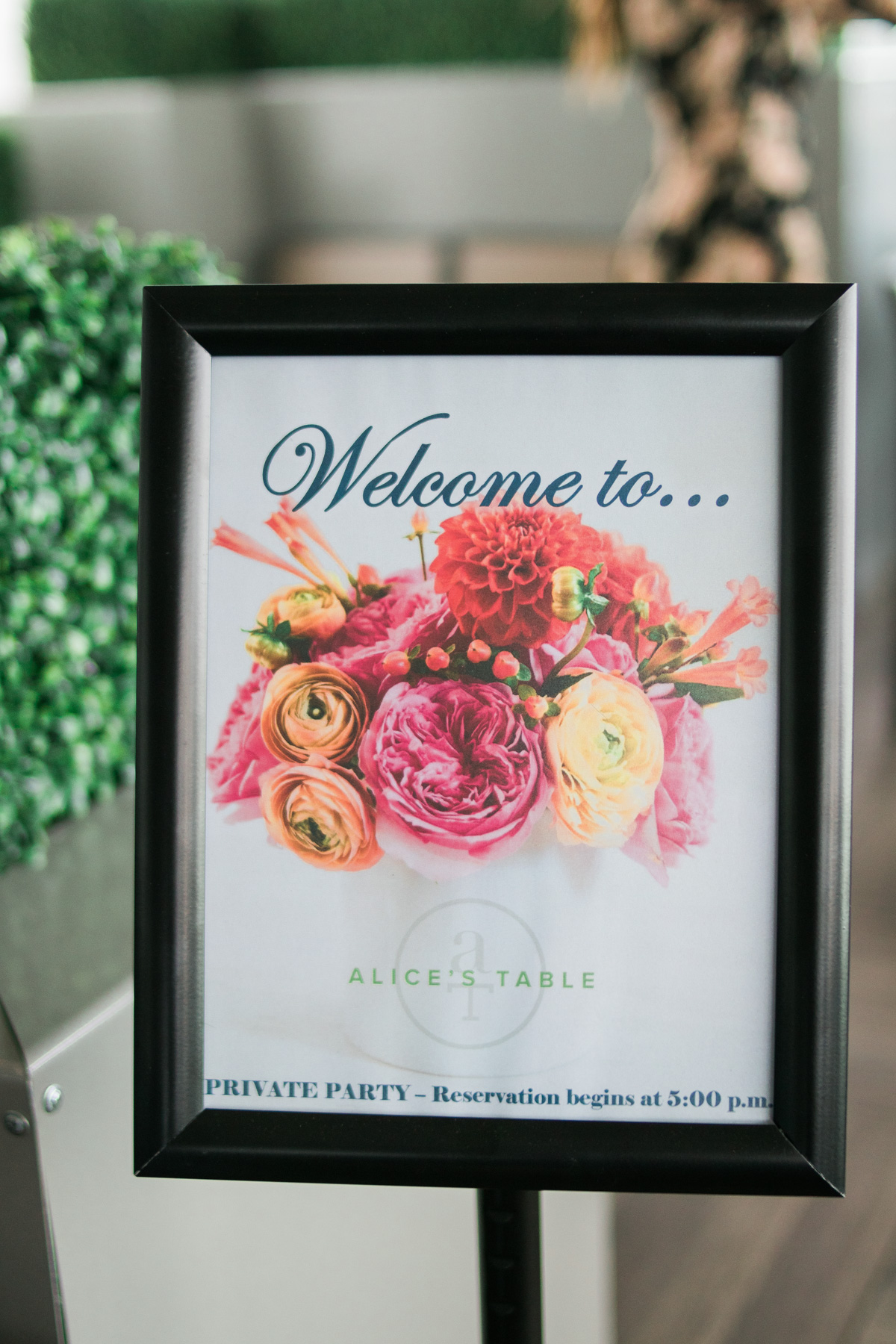 sign with flowers and text: Welcome to Alice's Table - Private Party - Reservation begins at 5:00pm