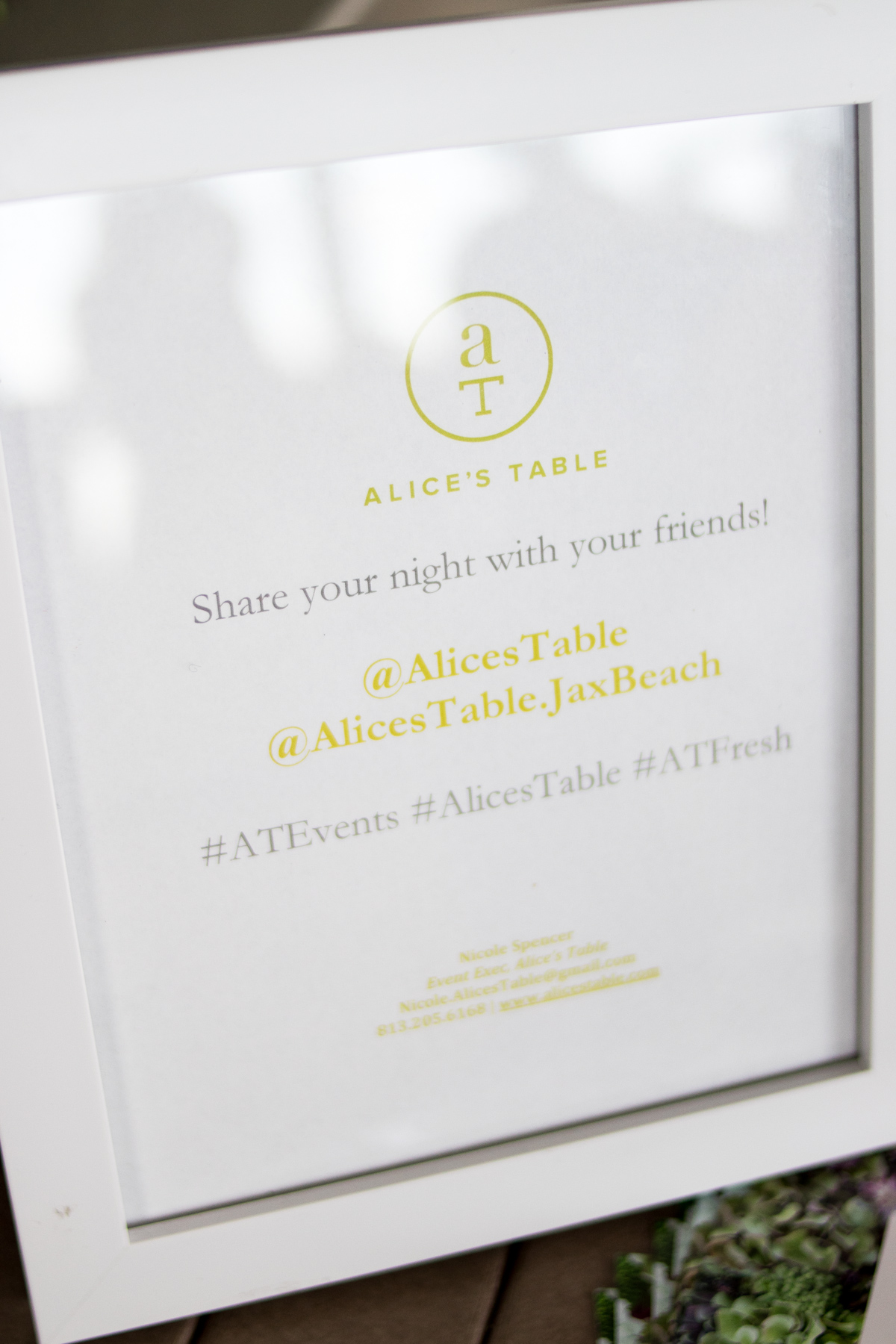 Sign with text: Alice's Table - Share your night with your friends! @AlicesTable @AlicesTable.JaxBeach #ATEvents #AlicesTable #ATFresh