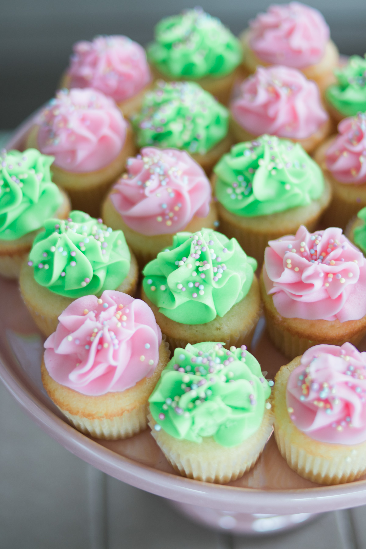 green and pink mini cupcakes with sprinkles on display