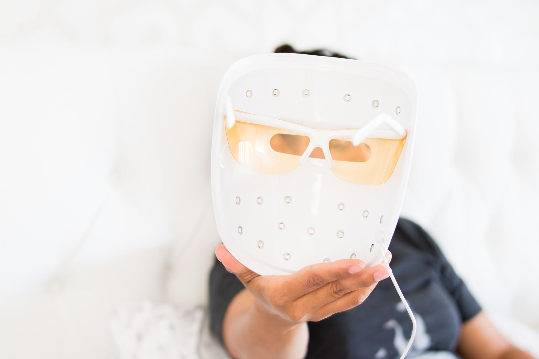 woman holding unlit Neutrogena Light Therapy acne mask