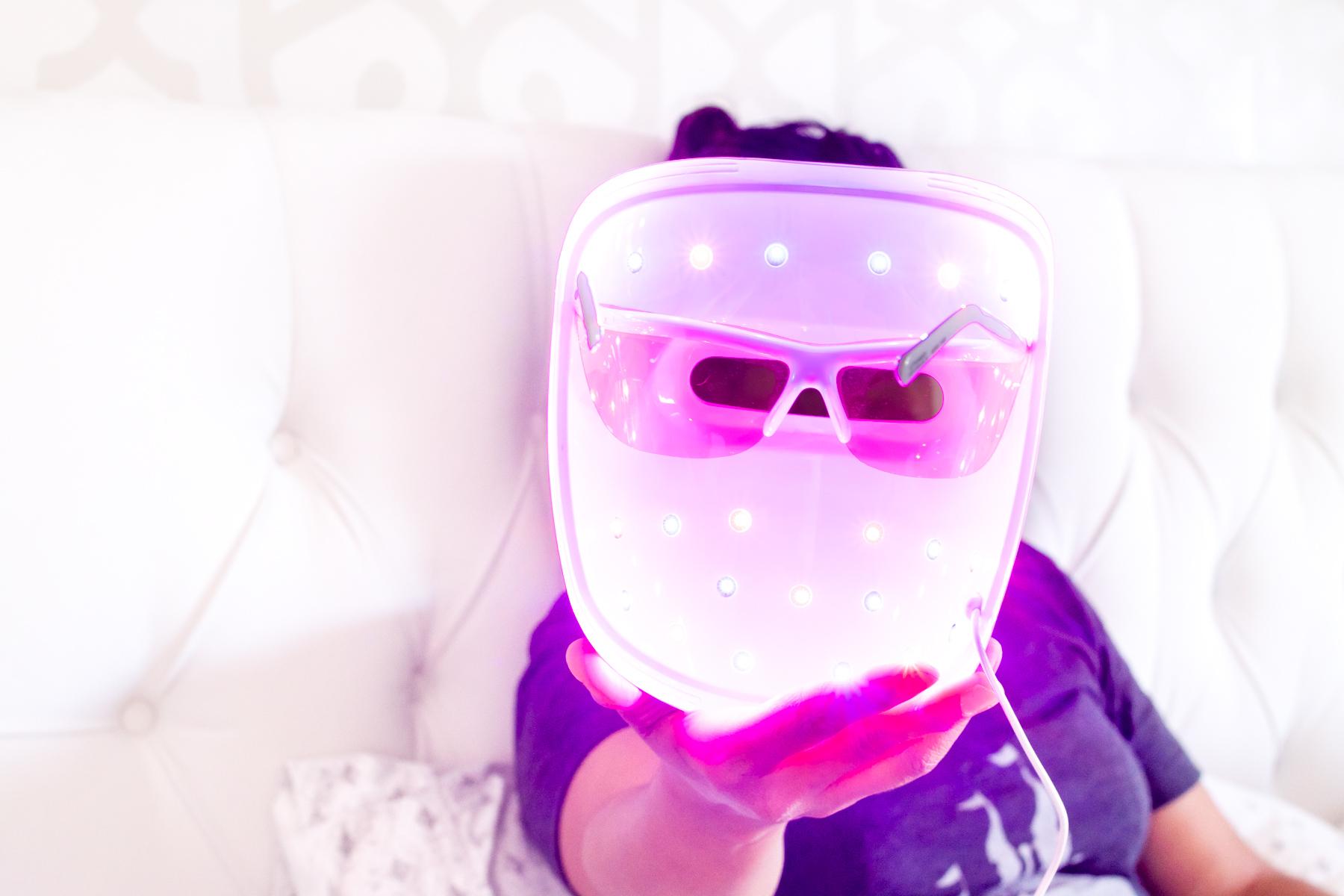 woman holding lit Neutrogena Light Therapy acne mask