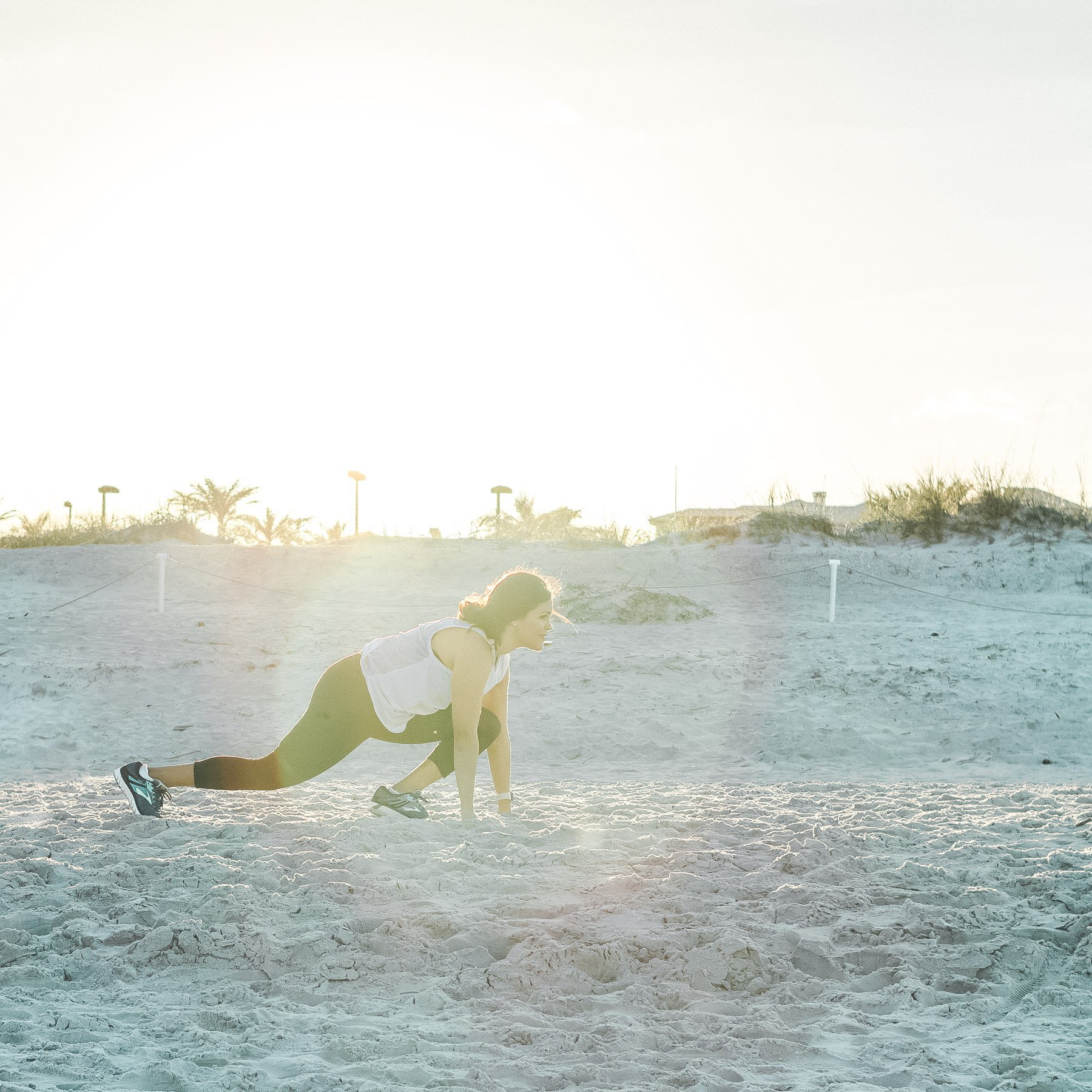 woman in sprint position at beach with solar flare behind her