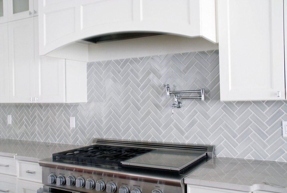 white kitchen with gray herringbone subway tile