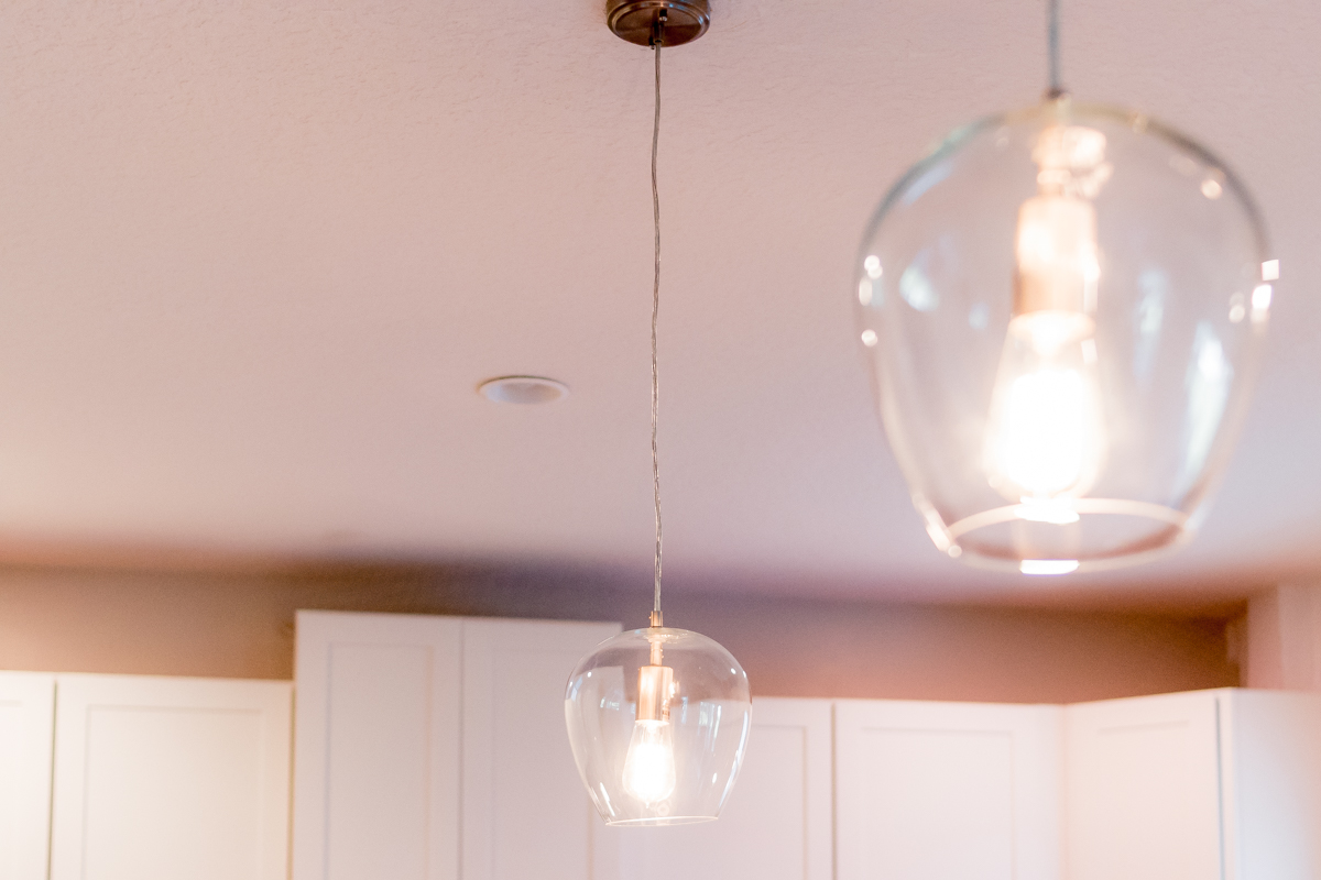 two lit glass pendants hanging in kitchen