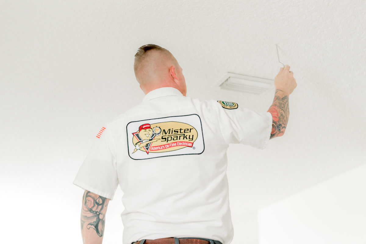 Mister Sparky electrician marking ceiling for installing kitchen pendant lights
