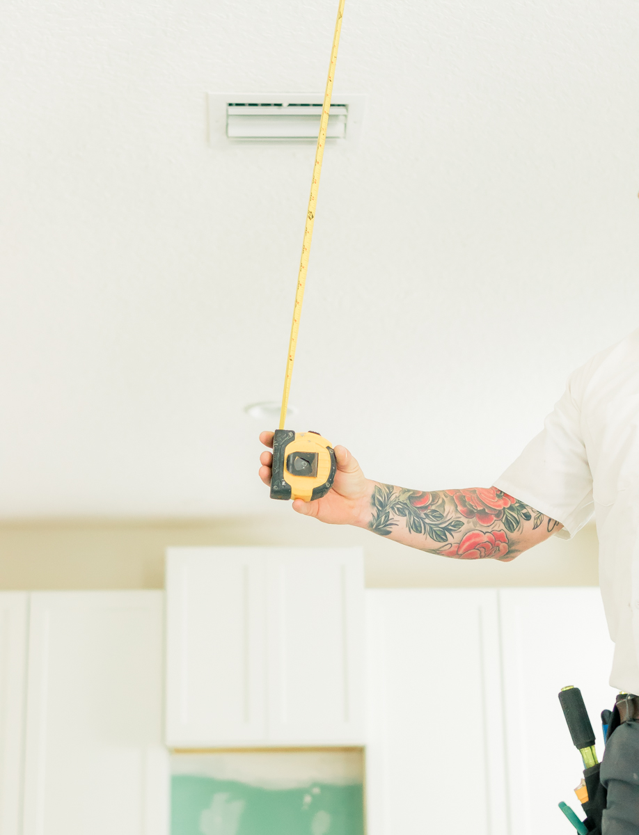 electrician with tattoos measuring ceiling for installation of kitchen pendant lights
