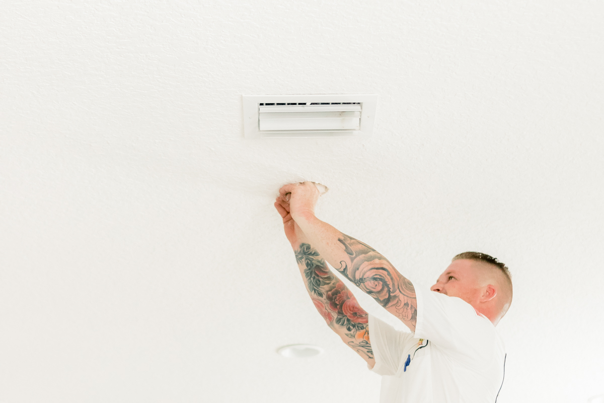 electrician with tattoos cutting drywall for pendant installation