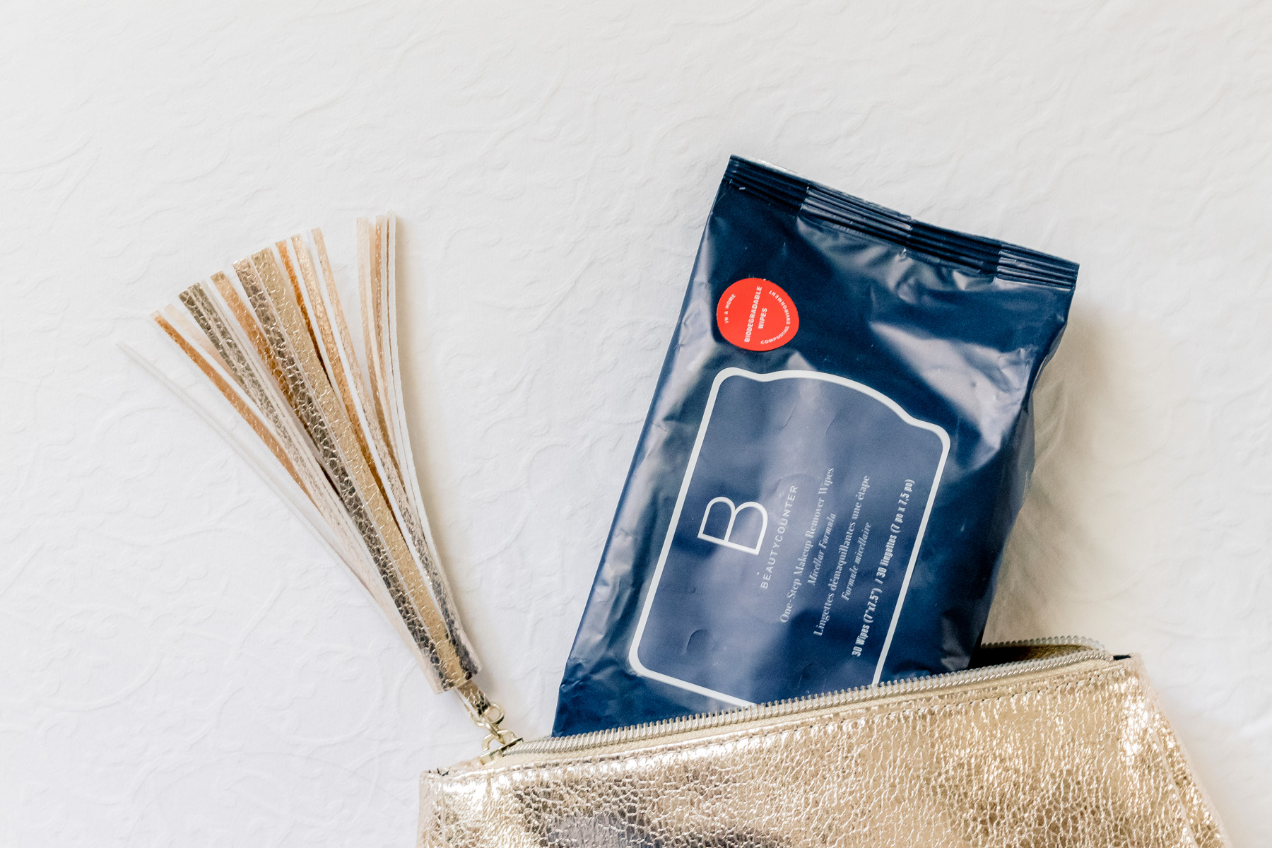 Beautycounter makeup removing wipes in a gold makeup bag