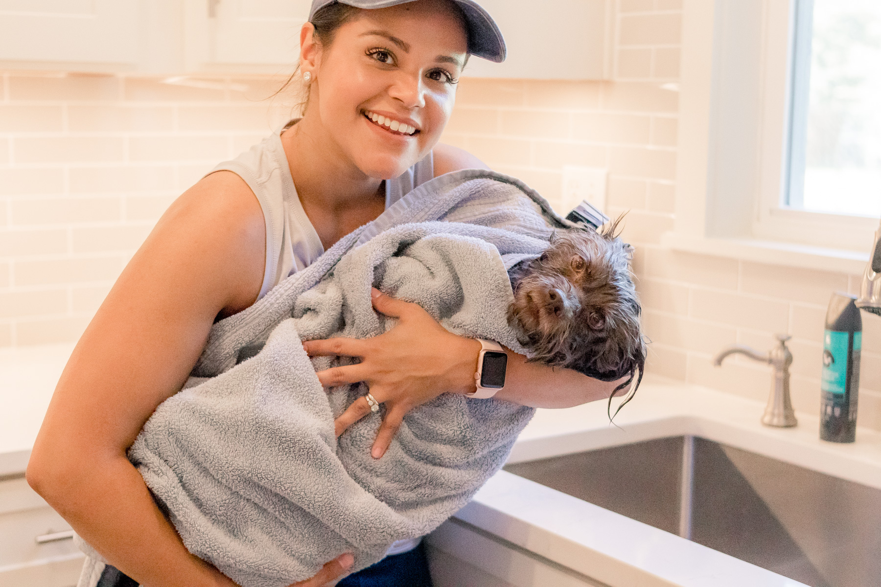 owner carrying dog wrapped in bath towel
