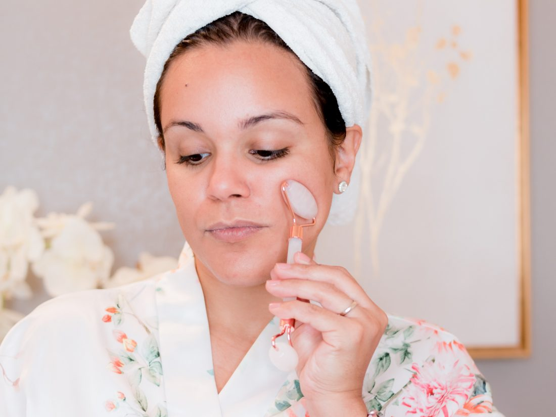 woman using rose quartz roller