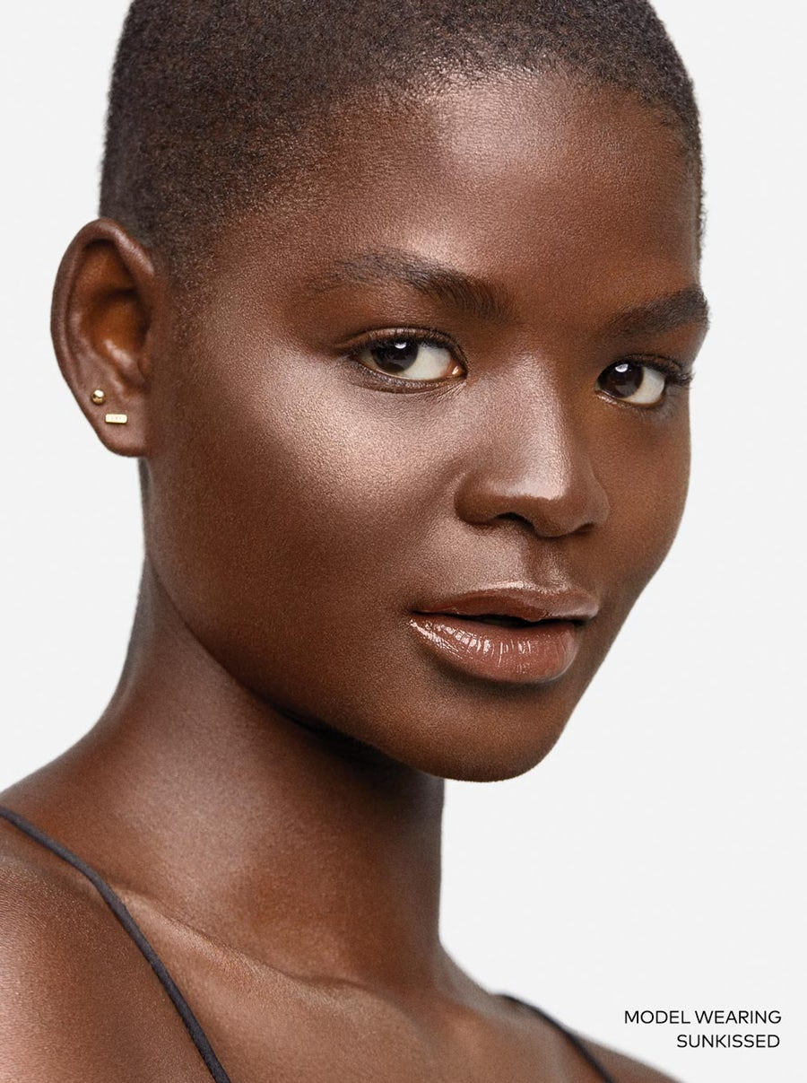 dark skinned model wearing Sunkissed Beautycounter highlighter