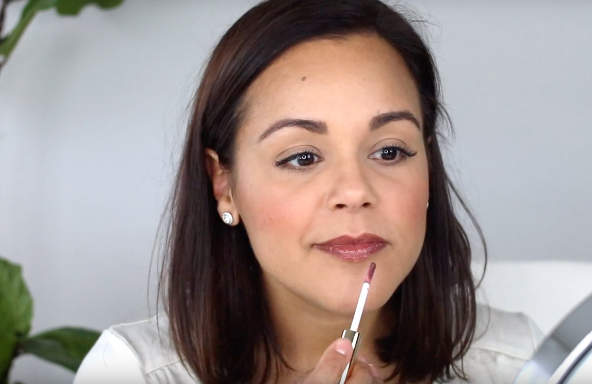 Lisette applying Beautycounter lip gloss in Fig
