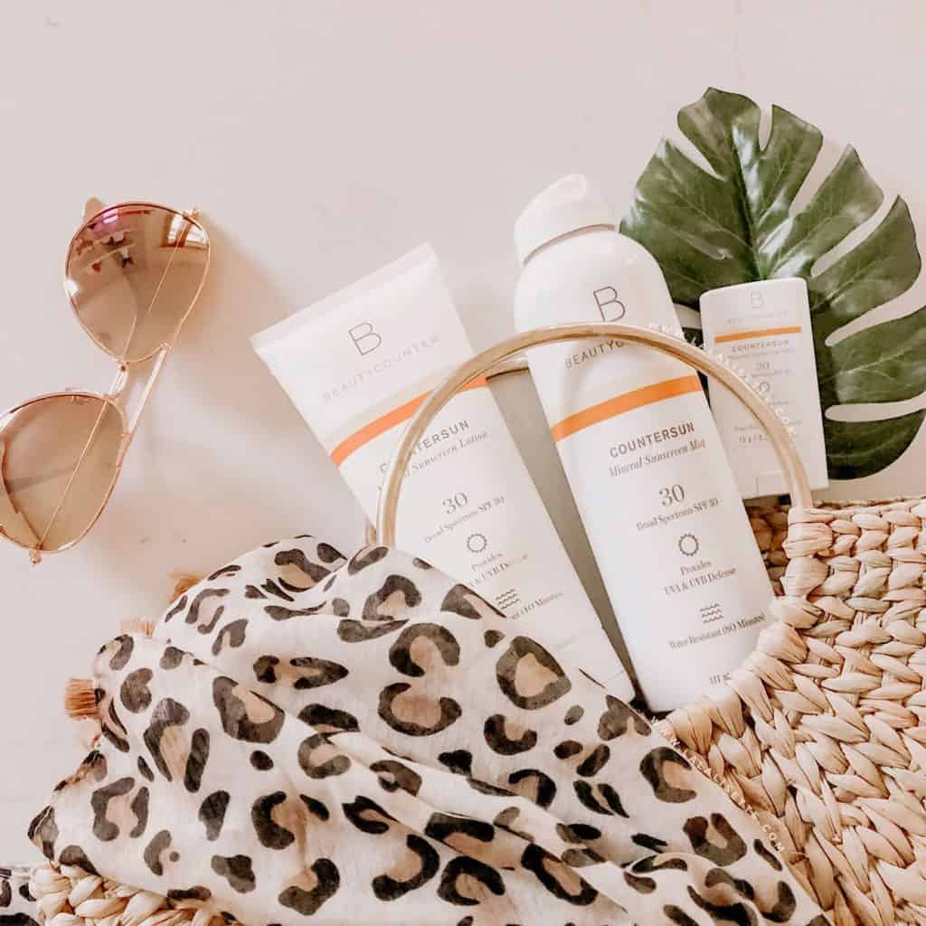 Beautycounter Countersun mineral sunscreens with straw bag and sunglasses - Why We Switched to Mineral Sunscreen