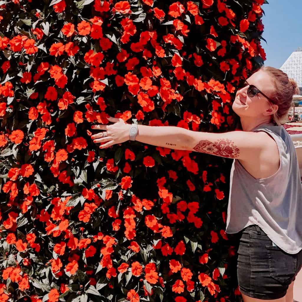 woman hugging floral display at  Epcot Flower & Garden Festival #FreshEpcot