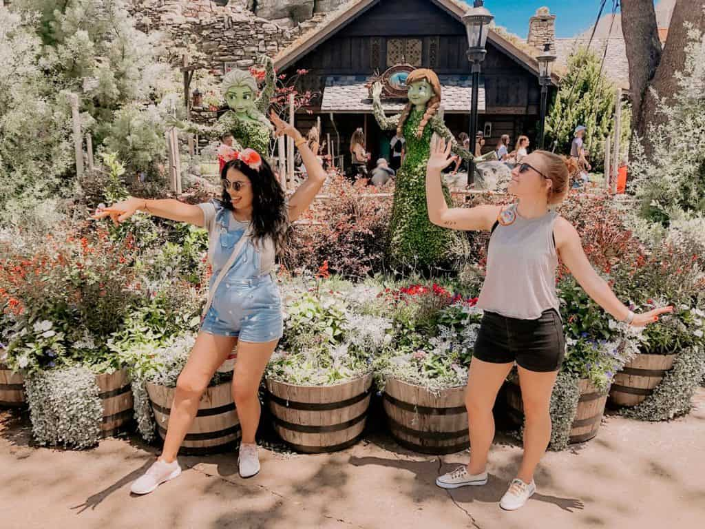 women posing in front of Elsa and Anna figurines in the Epcot Flower & Garden Festival at Disney