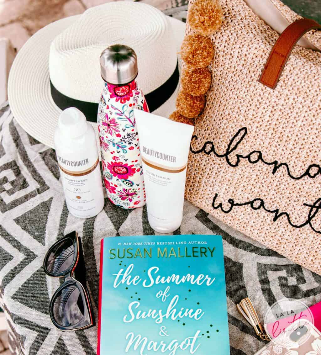 beach bag contents, including sunscreen, a beach read, water bottle, woven hat, and sunglasses