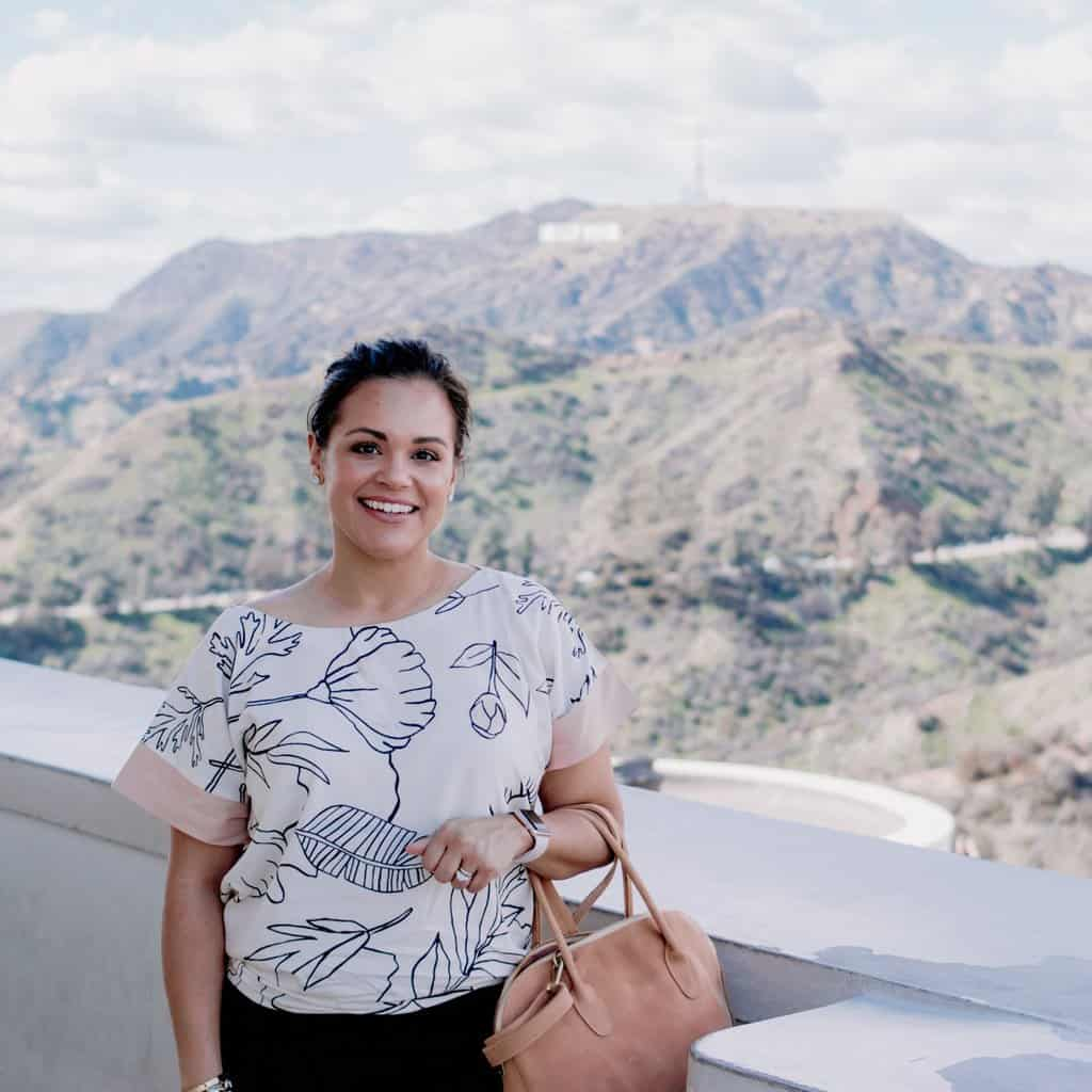 healthy living blogger La La Lisette wearing a Sseko reversible top and holding the Sseko Sheba handbag in oiled cognac with the Hollywood sign in the background