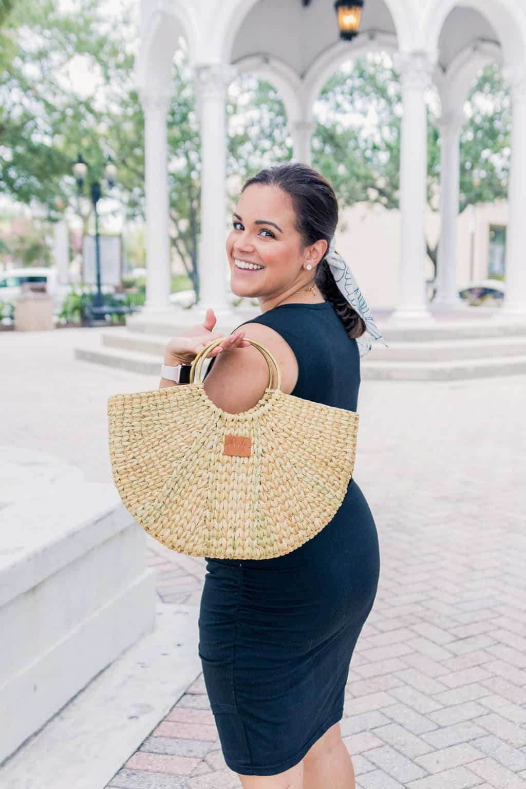 woman looking over the shoulder holding a Sseko Designs woven straw bag