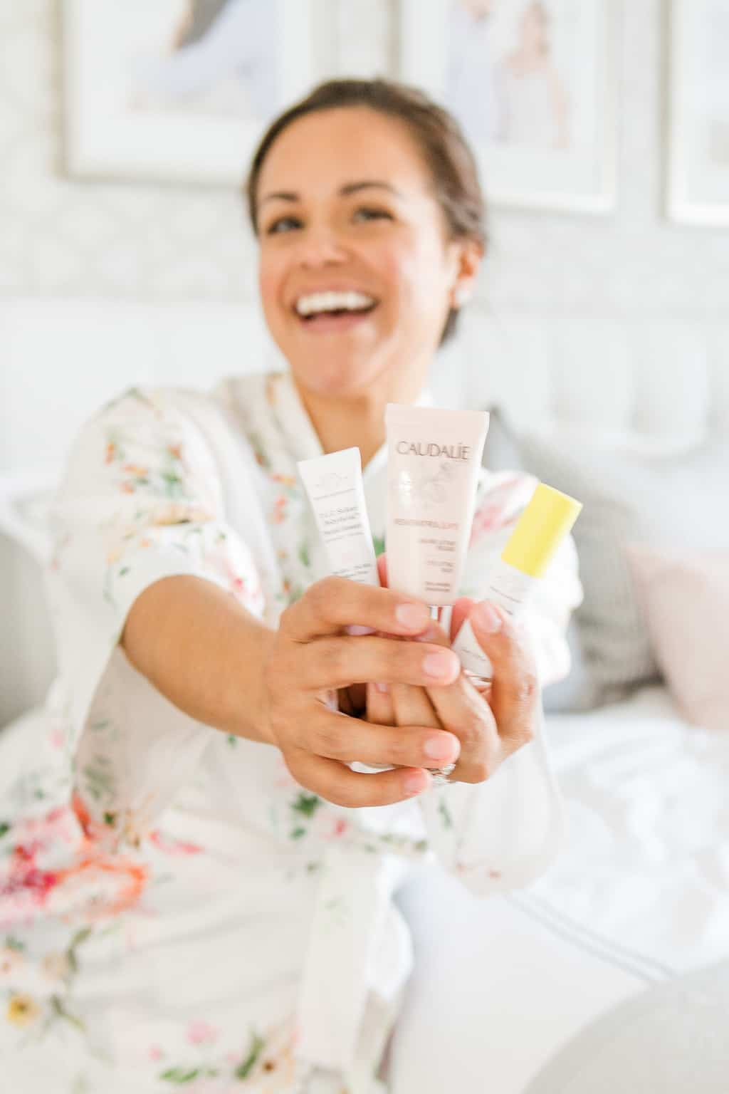 woman holding Drunk Elephant and Caudalie clean beauty products for oily skin
